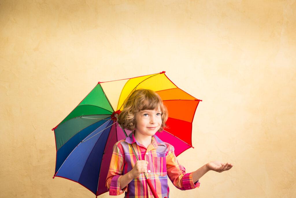 Kind schützt sich mit Regenschirm